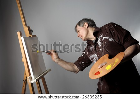 senior man painting on a canvas - stock photo