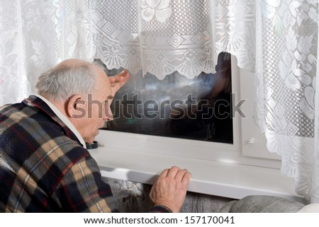 Senior man peering through a window at night as he watches for someone to arrive - stock photo