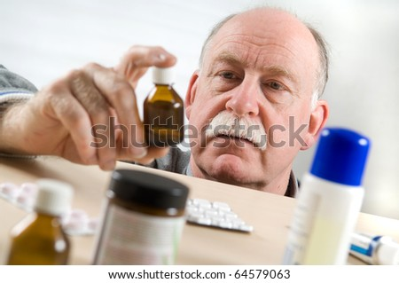 Senior man picking medicine bottle - stock photo