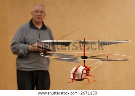 Senior man piloting tiny radio controlled helicopter indoors.  Shallow DOF with focus on helicopter. - stock photo