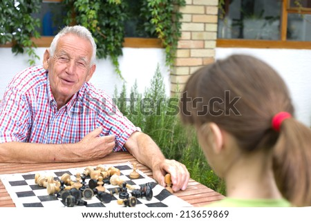 Senior man playing chess with her granddaughter in garden - stock photo