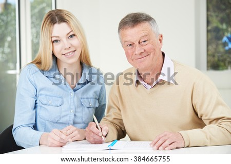 Senior Man Playing Completing Number Puzzle With Teenage Granddaughter - stock photo