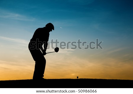 Senior man playing golf - pictured as a silhouette against an evening sky - stock photo