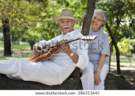 Senior man playing guitar while enjoying at park with mature woman - stock photo