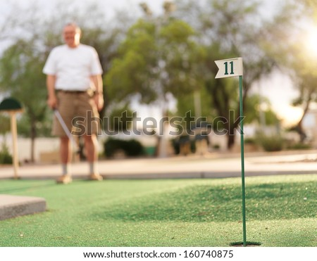 senior man playing mini golf - stock photo