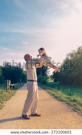 Senior man playing with adorable baby girl over a nature background. Grandparents and grandchild leisure time concept. - stock photo