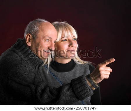 Senior man pointing at something to young woman on a dark red background