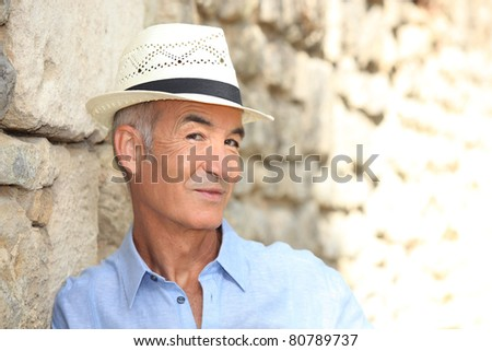 Senior man posing in a panama hat - stock photo