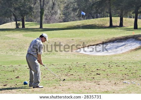 Senior man practicing golf game on the driving range. - stock photo