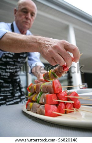 Senior man preparing fish kebabs on a terrace - stock photo