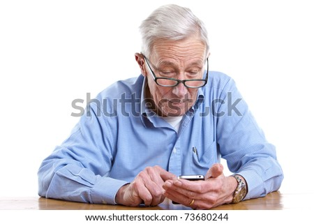 Senior man pulling a face while holding a mobile - stock photo