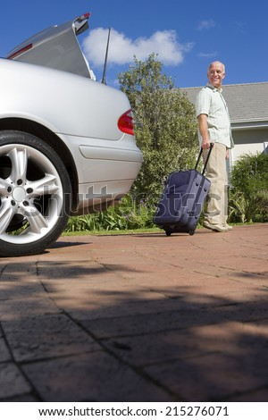 Senior man pulling suitcase on wheels from parked car boot on driveway, smiling, side view, portrait (surface level) - stock photo