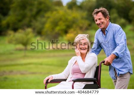 Senior man pushing woman in wheelchair, green autumn nature - stock photo
