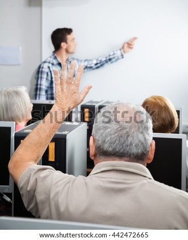 Senior Man Raising Hand In Computer Class