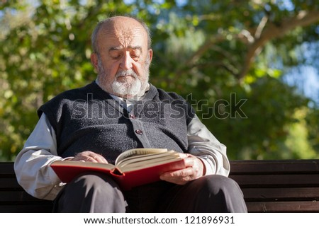 senior man reading a book in a park - stock photo
