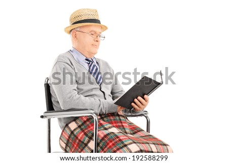Senior man reading a book seated in wheelchair isolated on white background - stock photo