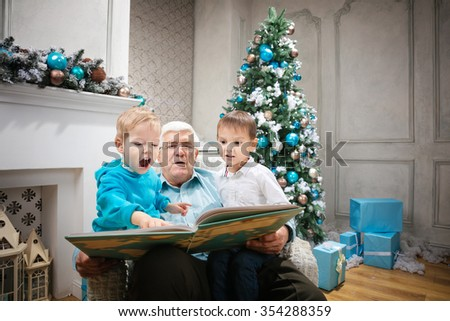 Senior man reading a book to grandsons at Christmas Eve - stock photo
