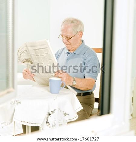 senior man reading a newspaper at home - stock photo