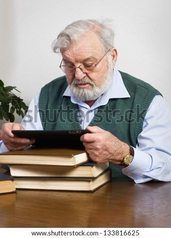 Senior man reading book on digital tablet - stock photo