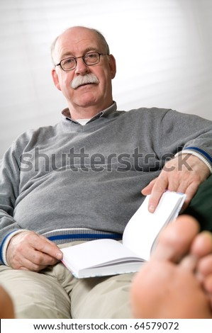 Senior man reading book while sitting on couch - stock photo