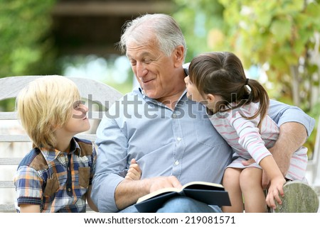 Senior man reading book with grandkids - stock photo