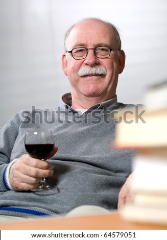 Senior man reading books while sitting on couch with a glass of wine - stock photo
