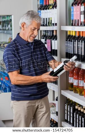 Senior man reading instructions from alcohol bottle at supermarket - stock photo