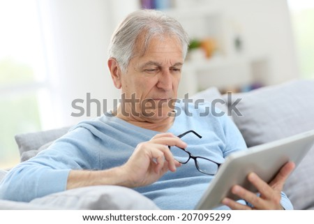 Senior man reading news on digital tablet  - stock photo
