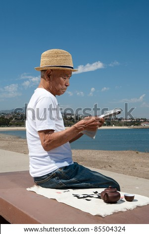 senior man reading newspaper on bench