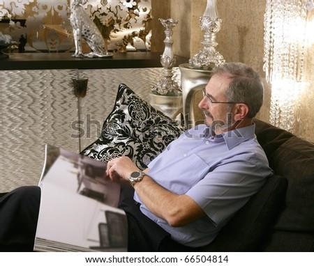 Senior man reading sofa luxury living room black and silver - stock photo