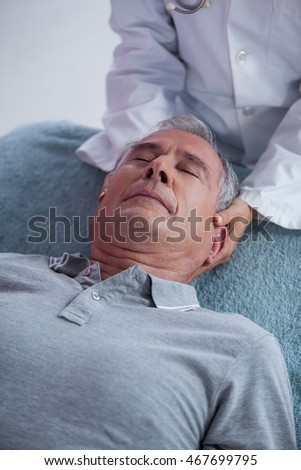 Senior man receiving neck massage from physiotherapist in clinic