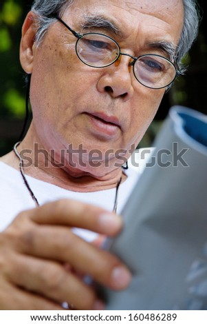 Senior man relaxing at home reading a book - stock photo