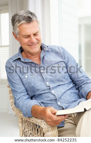 Senior man relaxing at home with a book - stock photo