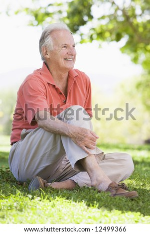 Senior man relaxing in countryside sitting on grass - stock photo