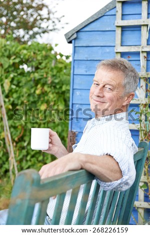 Senior Man Relaxing In Garden With Cup Of Coffee - stock photo