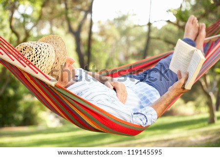 Senior Man Relaxing In Hammock With Book - stock photo