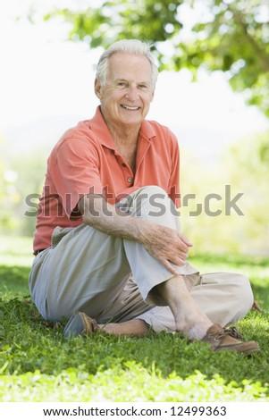 Senior man relaxing in park sitting on grass - stock photo