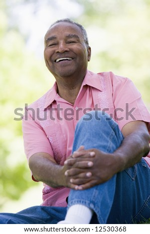 Senior man relaxing in park sitting on grass - stock photo