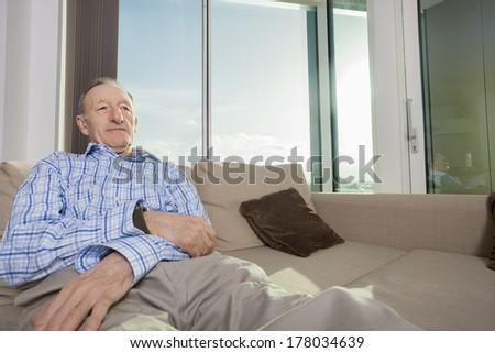 Senior man relaxing on sofa at home - stock photo