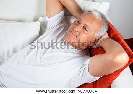 Senior man relaxing on sofa with hands behind his head - stock photo