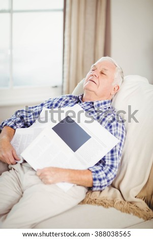 Senior man relaxing on sofa with newspaper in living room