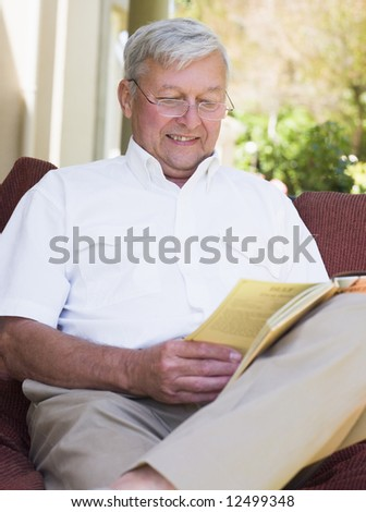 Senior man relaxing with book sitting on garden seat - stock photo