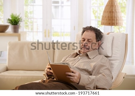 Senior man resting in chair at home, reading book.  - stock photo