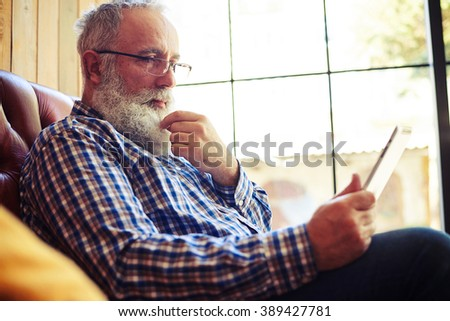 senior man resting on sofa and reading news on tablet pc at home
