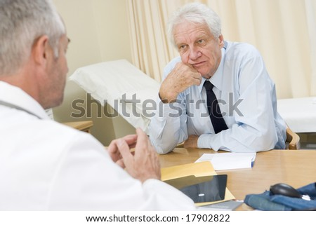 Senior man sat in doctors office - stock photo