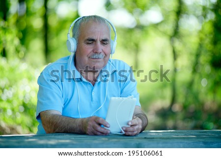 Senior man searching for an online or downloaded tune on his MP3 player or tablet as he sits outdoors in the garden wearing a set of headphones concentrating on the screen - stock photo