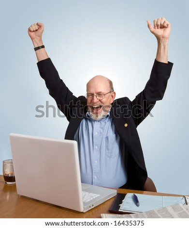 Senior man seated at desk, looking at computer, cheering over good news he has just received. - stock photo