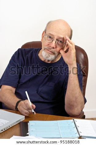Senior man seated at desk with laptop computer and checkbook, worried about paying the bills. - stock photo