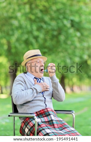 Senior man seated in wheelchair holding an inhaler and having an asthma attack - stock photo
