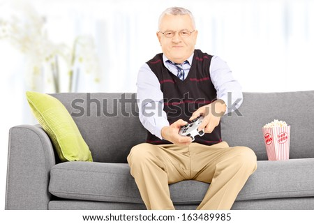 Senior man seated on a couch playing video games at home - stock photo